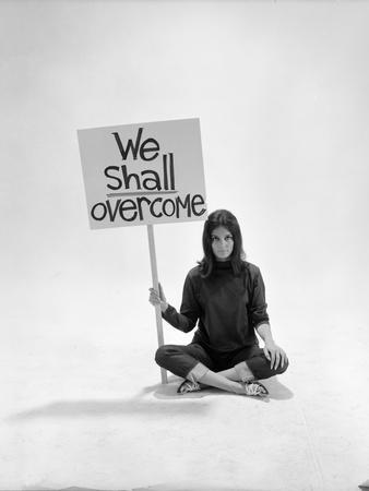 """Studio Photos of Gloria Steinem Sitting on Floor with Sign That Says 'We Shall Overcome"""", 1965"""