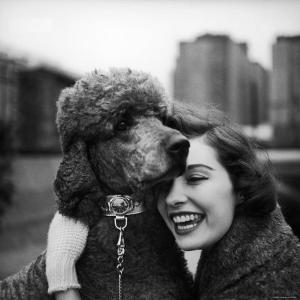 Woman Profiling a Big Smile While Adoring Her Poodle Wearing Large Swiss Watch on Dog Collar by Yale Joel