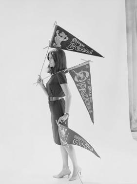 Writer Gloria Steinem Carrying Pennants for Professional Football Teams by Yale Joel