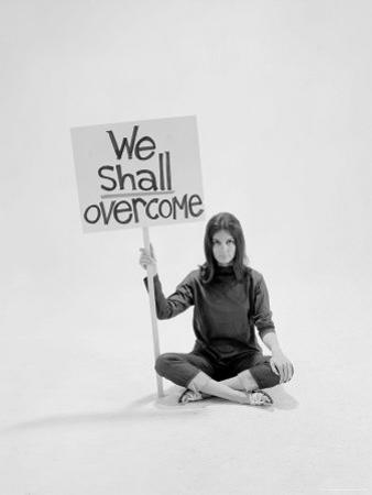 """Writer Gloria Steinem Sitting on Floor with Sign """"We Shall Overcome"""" Regarding Pop Culture by Yale Joel"""