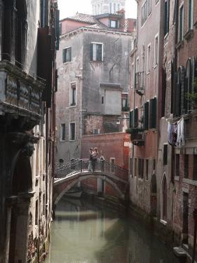Young Adult Couple Hugging and Kissing on Bridge over Canal, Venice, Italy