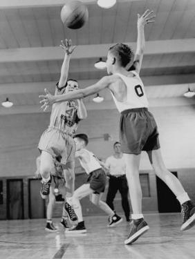Young Boy Shooting a Free-Throw Shot over the Head of Another Young Boy