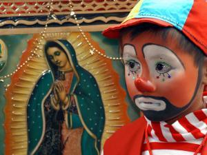 """Young Clown, """"Bolillito,"""" Stands Next to an Image of the Virgin of Guadalupe in Mexico City"""