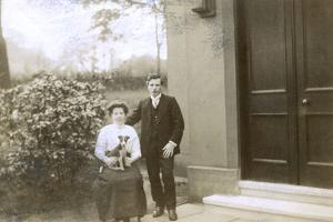 Young Couple and a Puppy in a Garden