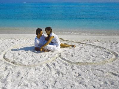 https://imgc.allpostersimages.com/img/posters/young-couple-on-beach-sitting-in-a-heart-shaped-imprint-on-the-sand-maldives-indian-ocean-asia_u-L-P91IJ30.jpg?p=0
