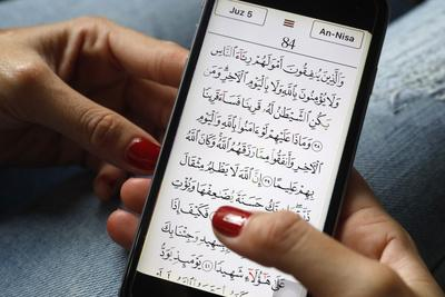 https://imgc.allpostersimages.com/img/posters/young-muslim-woman-reading-a-digital-quran-on-a-smartphone_u-L-Q1GYJDB0.jpg?artPerspective=n