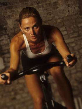 Young Woman Exercising on a Stationary Bike