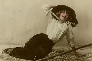 Young Woman in a Large Hat Sitting on Straw