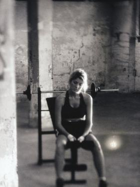 Young Woman Sitting on a Weight Bench