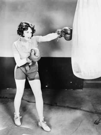 Young Woman with Boxing Gloves Trains with a Punching Bag