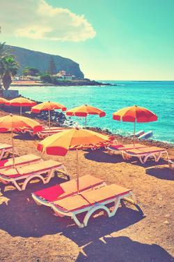 Vacant Umbrellas and Chaise Longues on a Sea Beach, Tenerife. Retro Style Filtered Image by Zoom-zoom