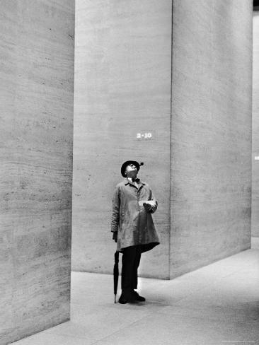 french actor jacques tati looking at the high ceiling of an office lobby reproduction. Black Bedroom Furniture Sets. Home Design Ideas