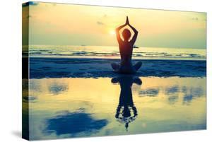 Yoga Woman Sitting In Lotus Pose On The Beach During Sunset by De Visu