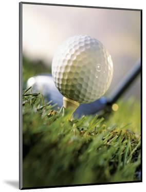 Golf Ball on Wooden Tee with Driver in Background by Eric Kamp