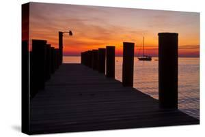 Sunrise on the Water with an Empty Dock and a Sailboat in the Distance of Tilghman Island, Maryland by Karine Aigner