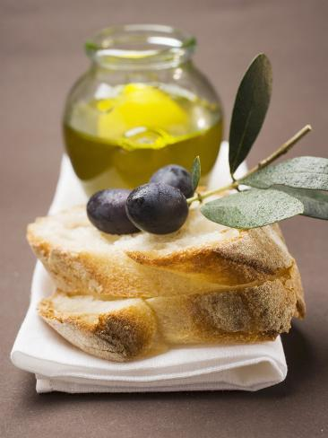 Olive Sprig with Black Olives on White Bread, Olive Oil Behind Fotografisk tryk