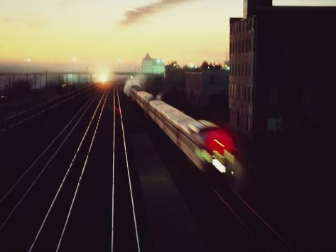 A Trans-Canada Railway Train Rushes Down the Tracks at Dusk Fotografisk tryk