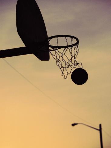 Silhouette of a Basketball Going Through a Basketball Net Fotografisk trykk