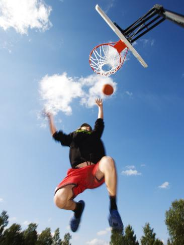 Low Angle View of a Basketball Player Slam Dunking Fotografie-Druck