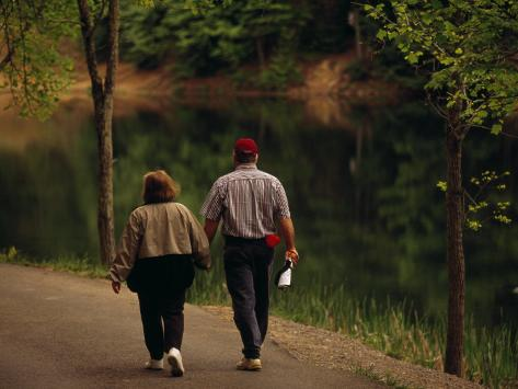 Couple Walking by the Water Along a Park Road Fotografie-Druck