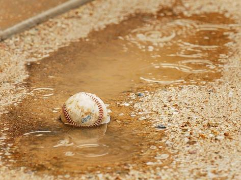 A Baseball Sits in a Puddle Photographic Print