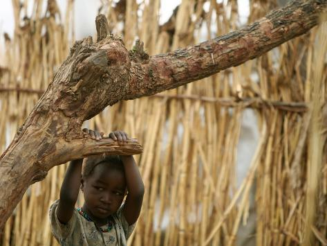 A Sudanese Girl Plays Inside a Thatched Hut at the Refugee Camp of Zamzam Photographic Print
