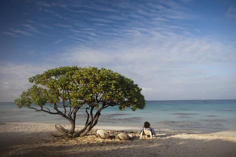 A Tourist Looks Out onto the Horizon from a Sandy Beach Photographic Print