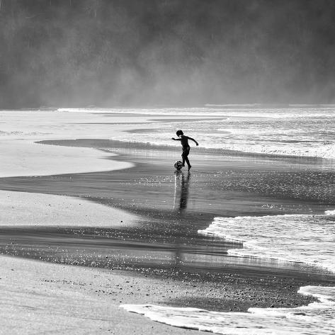 A Young Boy Kicks a Ball on Itamambuca Beach in Ubatuba, Brazil Photographic Print