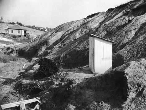An Outhouse in an Area That Is Plagued with Soil Erosion Photographic Print