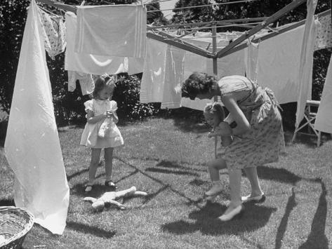 Suburban Mother Playing with Her Two Daughters While Hanging Laundry in Backyard Photographic Print