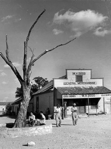 Two Boys Playing Nr. a Dead Tree as Judge Roy Langrty and a Man Walk Past a General Store Photographic Print