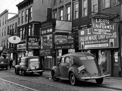 Cars Parked in Front of Four Navy Uniform Stores on Sand Street Photographic Print