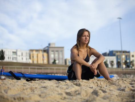 Woman Sitting on Beach with Surfboard at Bondi Beach Photographic Print
