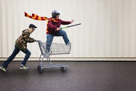 Two People Dressed up as Super Heroes or Characters Horsing around in a Shopping Cart with Goggles Photographic Print
