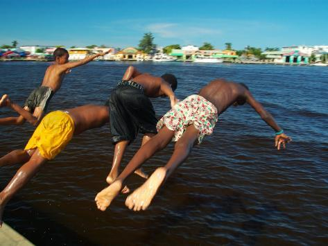 Young Boys Dive Off Marina at Bay of Belize with City in Background, Belize City, Belize Photographic Print