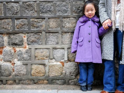 Young Girl Standing Against Stone Wall, Seoul, South Korea Photographic Print