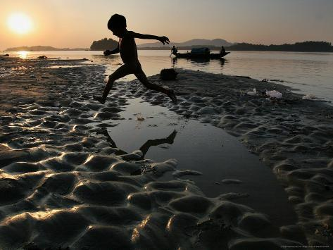 A Boy Plays on the Banks of the River Brahmaputra in Gauhati, India, Friday, October 27, 2006 Photographic Print