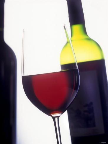 A Glass of Red Wine with a Bottle in the Background Photographic Print