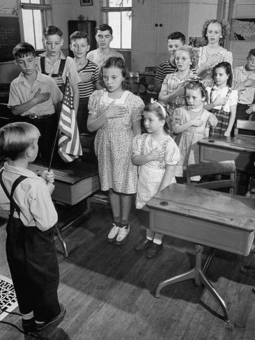 Children Reciting the Pledge of Allegiance as a Boy Holds the Us Flag in their Classroom Photographic Print