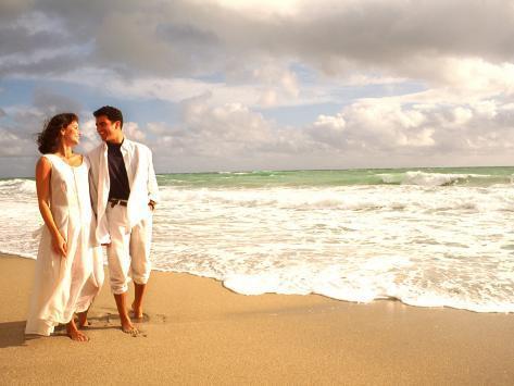 Hispanic Couple Walking Together on the Beach Photographic Print