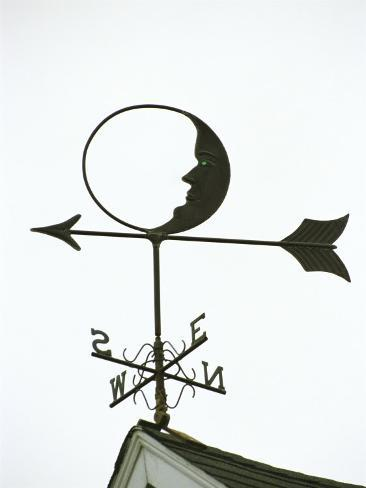 A Man-In-The-Moon Weather Vane on a Roof Top Photographic Print