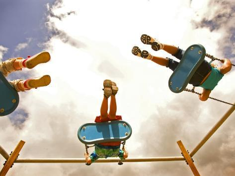 Children Playing on Swings from Below Photographic Print