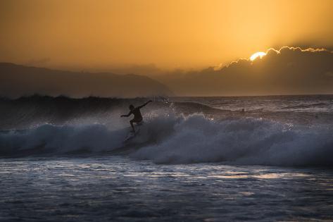 A Man Surfs at Sunset Valokuvavedos