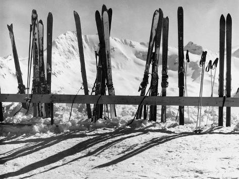 Skis Leaning Against a Fence in the Snow Photographic Print