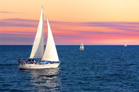 Sailboat Sailing towards Sunset on a Calm Evening Photographic Print