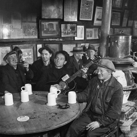 Woody Guthrie Playing and Singing for Patrons of Mcsorley's Bar Premium Photographic Print