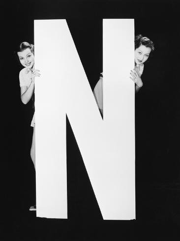 Two Women Hiding behind Huge Letter N Photographic Print