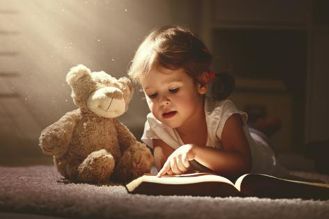 Child Little Girl Reading a Magic Book in the Dark Home with a Toy Teddy Bear Photographic Print