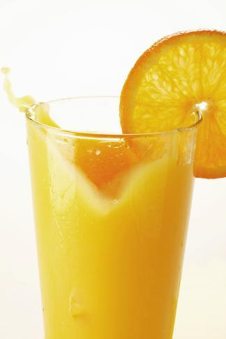 Orange Juice Splashing Out of Glass Photographic Print