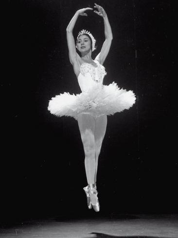 ballerina margot fonteyn in white costume leaping into the air while